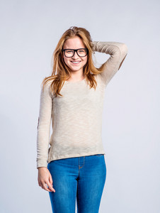 Teenage girl in jeans and brown long sleeved sweatshirt, young woman, studio shot on gray background