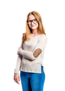 Teenage girl in jeans and brown long sleeved sweatshirt, young woman, studio shot on white background, isolated