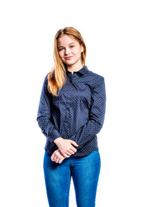 Teenage girl in jeans and dark blue dotted shirt, young woman, studio shot on white background, isolated