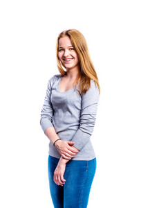 Teenage girl in jeans and gray t-shirt, young woman, studio shot on white background, isolated