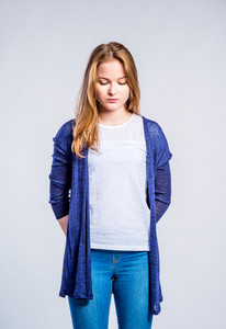 Teenage girl in jeans and long blue sweater, young woman, studio shot on gray background