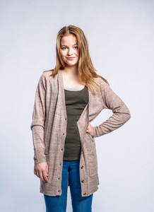 Teenage girl in jeans and long brown sweater, young woman, hand on hipstudio shot on gray background