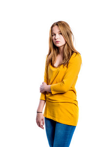Teenage girl in jeans and long sleeved yellow t-shirt, young woman, studio shot on white background, isolated