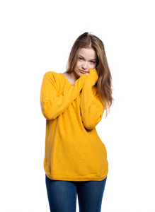 Teenage girl in jeans and mustard yellow sweater. Young woman, studio shot on white background, isolated.