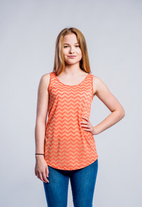 Teenage girl in jeans and orange tank top, young woman, studio shot on gray background