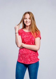 Teenage girl in jeans and red t-shirt, young woman, studio shot on gray background