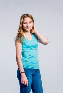 Teenage girl in jeans and turquoise t-shirt, young woman, studio shot on gray background