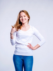 Teenage girl in jeans and white long sleeved t-shirt, young woman, studio shot on gray background