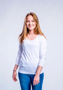 Teenage girl in jeans and white long sleevedt-shirt, young woman, studio shot on gray background