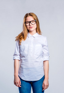 Teenage girl in jeans and white shirt, young woman, studio shot on gray background