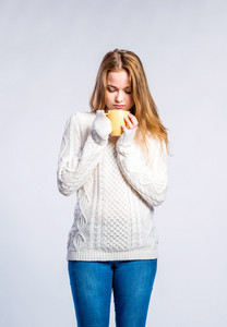 Teenage girl in jeans and white sweater, holding a cup with hot drink, young woman, studio shot on gray background