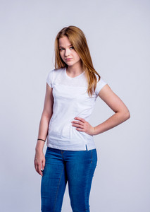 Teenage girl in jeans and white t-shirt, young woman, studio shot on gray background