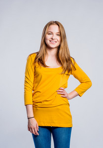 Teenage girl in jeans and yellow long sleeved t-shirt, young woman, studio shot on gray background