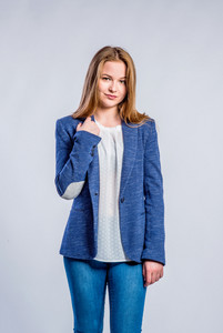 Teenage girl in jeans, white blouse and blue jacket, young woman, studio shot on gray background