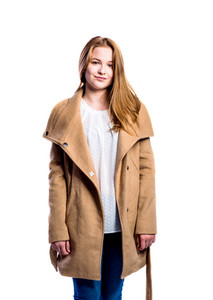 Teenage girl in jeans, white blouse and brown coat, young woman, studio shot on white background, isolated