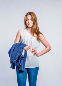 Teenage girl in jeans, white sleeveless blouse, holding a blue jacket, young woman, studio shot on gray background
