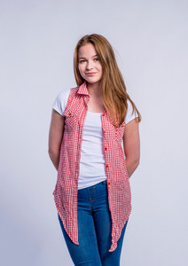 Teenage girl in jeans, white t-shirt and red checked shirt young woman, studio shot on gray background