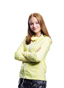 Teenage girl in neon yellow running jacket and fitness leggings, crossed arm, woman, studio shot on white background, isolated