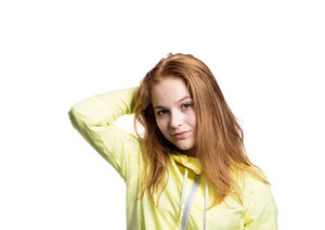 Teenage girl in neon yellow running jacket, holding head. Beautiful sportswoman. Studio shot on white background, isolated.