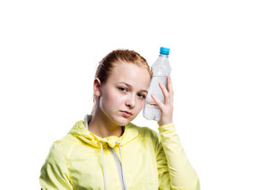 Teenage girl in neon yellow running jacket, holding water bottle. Beautiful sportswoman. Studio shot on white background, isolated.