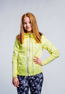 Teenage girl in neon yellow sweatshirt and fitness leggings, arm on hip, young woman, studio shot on gray background