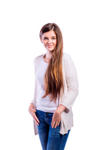 Teenage girl in white t-shirt, long sweater and jeans, hands in pockets, young beautiful woman, studio shot on white background, isolated
