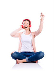 Teenage girl in white t-shirt, pink cardigan and jeans, sitting on the floor, earphones on head, arm raised, listening music, young beautiful woman, studio shot on white background, isolated