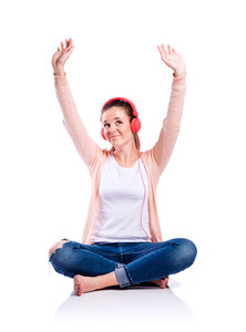 Teenage girl in white t-shirt, pink cardigan and jeans, sitting on the floor, earphones on head, arms raised, listening music, young beautiful woman, studio shot on white background, isolated