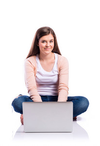 Teenage girl in white t-shirt, pink cardigan and jeans, working on laptop, sitting on the floor, young beautiful woman, studio shot on white background, isolated