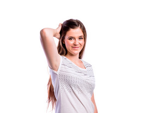 Teenage girl in white t-shirt, touching hair. Young beautiful woman, studio shot on white background, isolated.