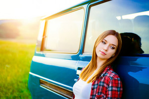 Teenage girl with long hair smiling leaning against green campervan outside in sunny nature