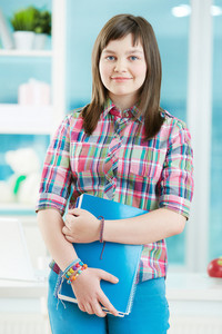Teenage girl with notepad looking at camera with smile