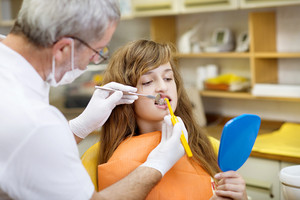 Teenage girl with the braces on her teeth is having a treatment at dentist