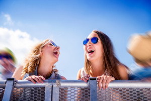 Teenage girls at summer music festival standing under the stage at the crowd control barrier, laughing