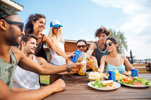 Teenage happy friends having picnic party outdoors
