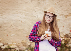 Teenage hipster girl enjoying her take away drink walking down the city street