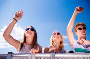 Teenagers at summer music festival, standing under the stage at the crowd control barrier, enjoying themselves, arms raised