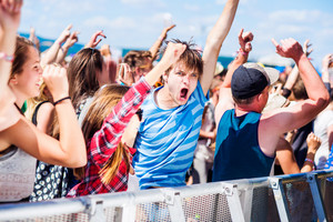 Teenagers at summer music festival under the stage in a crowd enjoying themselves, arm raised