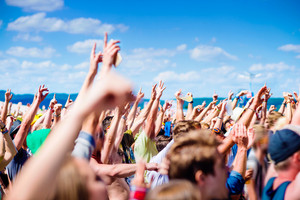 Teenagers at summer music festival under the stage in a crowd enjoying themselves, clapping and singing