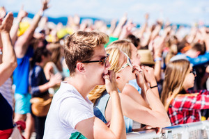 Teenagers at summer music festival under the stage in a crowd enjoying themselves, whistling