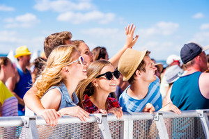 Teenagers at summer music festival under the stage in a crowd enjoying themselves