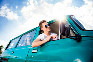 Teenagers inside an old campervan on a roadtrip, boy leaning out of window, sunny summer day