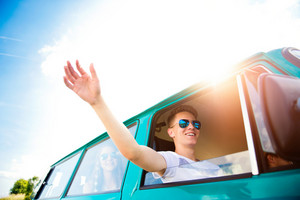 Teenagers inside an old campervan on a roadtrip, boy  stretching hand out of window, sunny summer day