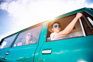 Teenagers inside an old campervan on a roadtrip, sunny summer day