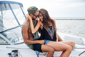Tender young couple sitting and hugging on boat