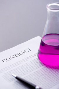 Test-tube with purple liquid over paper agreement