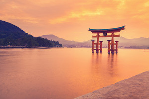 The famous orange floating shinto gate (Torii) of Itsukushima shrine, Miyajima island of Hiroshima prefecture, Japan at sunset.