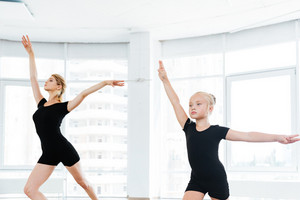 The silhouettes of little ballerina and personal classic ballet teacher in studio dancing