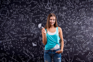 Thinking girl  in blue singlet holding her head against big blackboard with mathematical symbols and formulas, back view, rear view