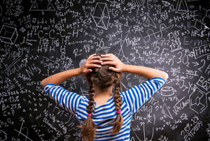 Thinking girl  in blue striped t-shirt with two braids holding her head against big blackboard with mathematical symbols and formulas, back view, rear viewpoint